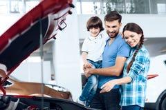 Una familia joven vino a la sala de exposición del coche elegir un nuevo coche Imagen de archivo libre de regalías