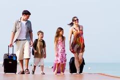 Una familia joven y atractiva con sus equipajes. Fotografía de archivo