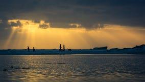 Una familia que camina su perro en la playa en la puesta del sol imagen de archivo libre de regalías