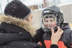 Una familia que juega en la pista de patinaje en invierno Fotos de archivo libres de regalías
