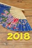Una fan azul de la mano con 2018 por el Año Nuevo chino Imágenes de archivo libres de regalías