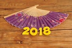 Una fan púrpura de la mano con 2018 por el Año Nuevo chino Imagen de archivo libre de regalías