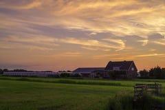 Una fattoria olandese dal lato del paese al tramonto/al crepuscolo Fotografia Stock
