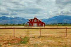 Una fattoria rossa in una valle con Rocky Mountains nei precedenti fotografia stock