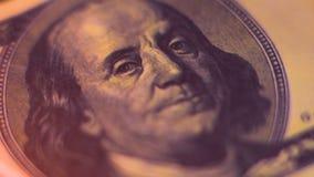 Una fattura del cento-dollaro con un ritratto di Benjamin Franklin è su fuoco stock footage