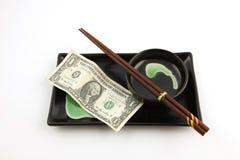 Una fattura del dollaro di Stati Uniti su una zolla dei sushi Immagine Stock