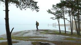 Una fauna de observación del hombre de mediana edad a través de los prismáticos en una orilla rocosa del mar en una mañana brumos almacen de video