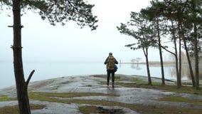 Una fauna de observación del hombre de mediana edad a través de los prismáticos en una orilla rocosa del mar en una mañana brumos metrajes