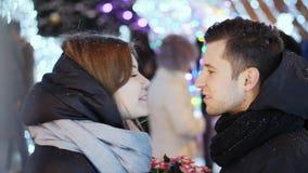 Una fecha con un par hermoso bajo nevadas, el hombre da flores y un regalo a una mujer por Año Nuevo almacen de metraje de vídeo