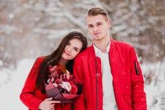 Una fecha de amantes con mi parque en el invierno Un ramo de flores rojas, paseo, abrazo, beso, risa en un ajuste romántico imagenes de archivo