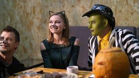 Una fecha en el estilo del partido de Halloween, los individuos con una muchacha vestida en trajes y con un maquillaje terrible e metrajes