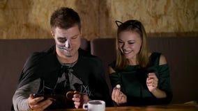 Una fecha en el estilo del partido de Halloween, un individuo con una muchacha vestida en trajes y con un maquillaje terrible est almacen de video