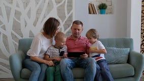 Una felice famiglia caucasica usa una tavoletta digitale in salotto a casa video d archivio