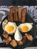 Una feliz cara sonriente, una cara hecha de la comida, con los ojos de huevos fritos con las yemas de huevo, una boca de la carne imagen de archivo libre de regalías