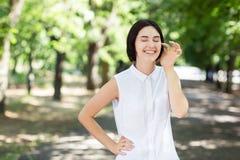 Una femmina allegra su uno sfondo naturale Una bella ragazza di risata che tocca il suo fronte Una signora sveglia divertendosi i Fotografia Stock Libera da Diritti