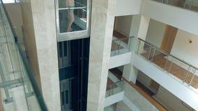 Una femmina sta stando in ascensore commovente di vetro archivi video