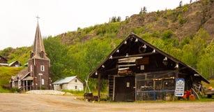 Una ferretería vieja y una iglesia situadas al lado de un río en Canadá septentrional foto de archivo libre de regalías