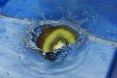 Una fetta di caduta del kiwi nell'acqua piacevole Fotografia Stock