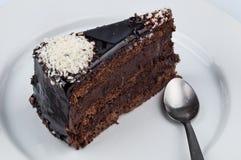 Una fetta di dolce di cioccolato con la guarnizione lucida dello sciroppo del cioccolato Fotografie Stock Libere da Diritti