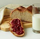 Una fetta di pane, diffusione con l'inceppamento di lampone e un bicchiere di latte Immagine Stock