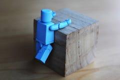 Una figura che scala un cubo di legno immagini stock