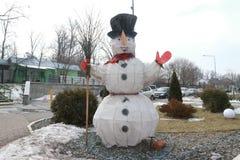 Una figura di un pupazzo di neve con una scopa nell'iarda Fotografie Stock
