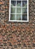 Una figura fantasmal que mira hacia fuera de una ventana vieja Fotos de archivo