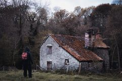 Una figura incappucciata che sta fuori di un granaio abbandonato nella campagna nell'inverno, con un freddo, annata pubblica fotografia stock