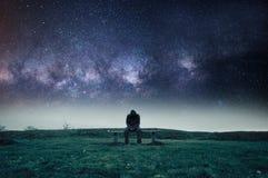 Una figura incappucciata sola che si siede su un banco di parco, sembrante triste, solo e depresso Con le stelle e l'universo qui immagini stock libere da diritti