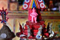 Una figura rosa di un uomo, adattata da una pasta, su un altare buddista in un monastero, un puja festivo, un'offerta alle protez Fotografie Stock