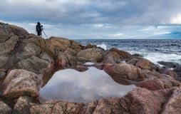 Una figura solitaria de un fotógrafo con un trípode en una orilla pedregosa del océano Imágenes de archivo libres de regalías