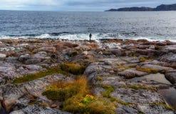 Una figura solitaria de un fotógrafo con un trípode en una orilla pedregosa del océano Fotos de archivo