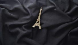 Una figurilla de la torre Eiffel en un fondo negro de la tela imagen de archivo