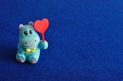 Una figurina dell'ippopotamo che tiene un cuore rosso Immagine Stock