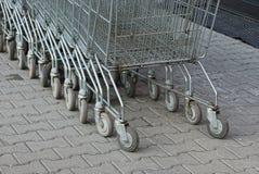 Una fila de carros de la compra grises de un soporte del supermercado en la calle en la acera imagenes de archivo