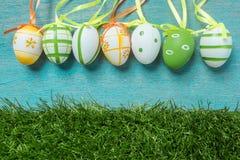 Una fila de cinco huevos de Pascua coloridos en fondo e hierba azules Fotografía de archivo libre de regalías