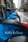 Una fila de Citibikes en una calle de New York City en un día lluvioso Fotografía de archivo libre de regalías