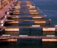 Una fila de 13 embarcaderos vacíos del barco en el agua Fotografía de archivo libre de regalías