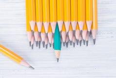 una fila de lápices simples amarillos en un fondo y ligero verdes fotos de archivo libres de regalías