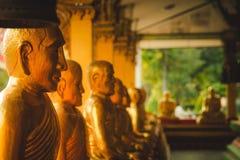 Una fila de la estatua de oro de Buda en Wat Intharam Kanchanaburi, tailandesa foto de archivo