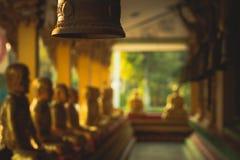 Una fila de la estatua de oro de Buda en Wat Intharam Kanchanaburi, tailandesa fotografía de archivo