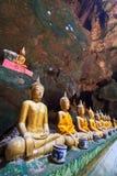 Una fila de las estatuas de Buda en la cueva Fotos de archivo