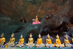 Una fila de las estatuas de Buda en la cueva Imagen de archivo