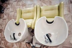 una fila de los fregaderos que se lavan del pelo lavabos blancos para el peluquero fotos de archivo libres de regalías