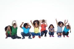 Una fila de los niños que se agachan abajo junto Foto de archivo