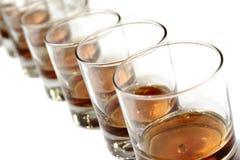 Una fila de los vidrios del whisky Imágenes de archivo libres de regalías