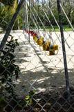 Una fila de oscilaciones en un parque Fotografía de archivo