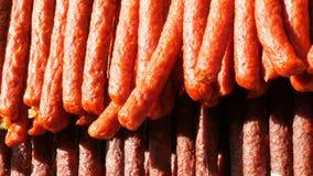Una fila de salchichas ahumadas está colgando en el escaparate de una carnicería almacen de video
