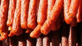 Una fila de salchichas ahumadas está colgando en el escaparate de una carnicería metrajes
