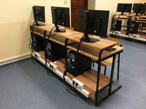 Una fila de sillas, de ordenadores y de monitores en la tabla en la sala de clase vacía fotos de archivo